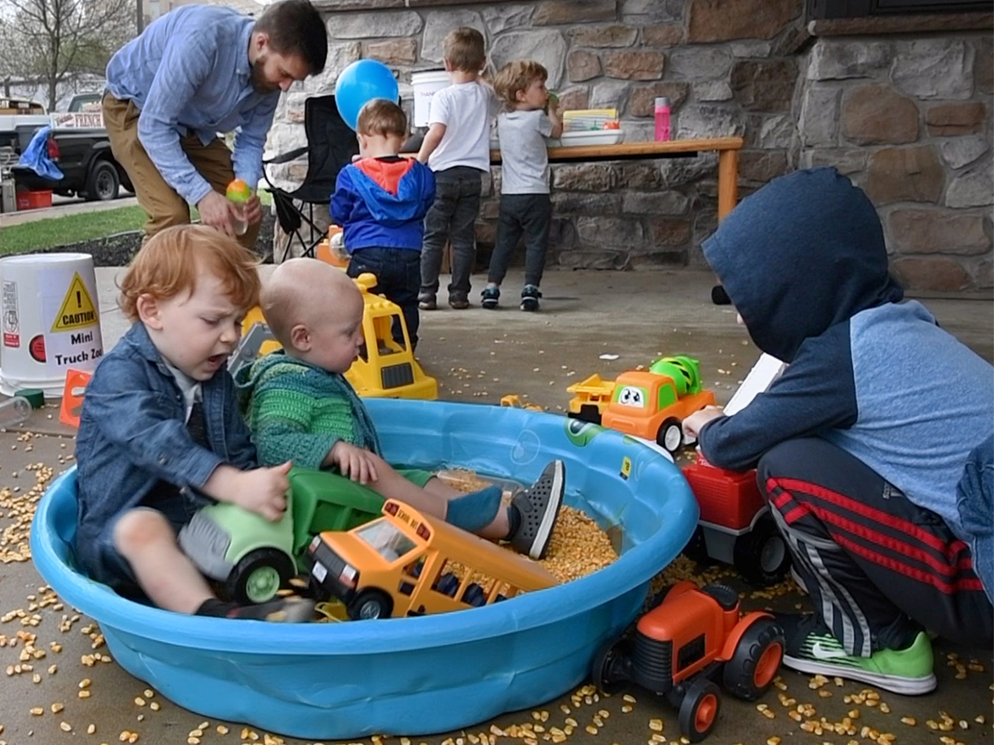Children play in a corn box with toy trucks after experiencing real ones during the Truck Zoo at Paul Smith Library of Southern York County.