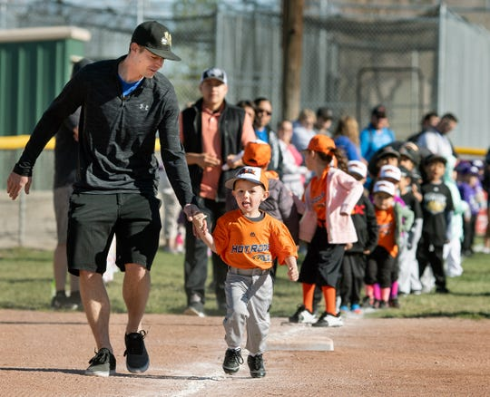 Pierce Cooper, 3, and his father Blake lead off running the bases during the player introductions.