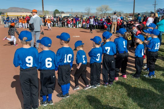 T-ball and farm teams watch as players run the bases during player introductions.