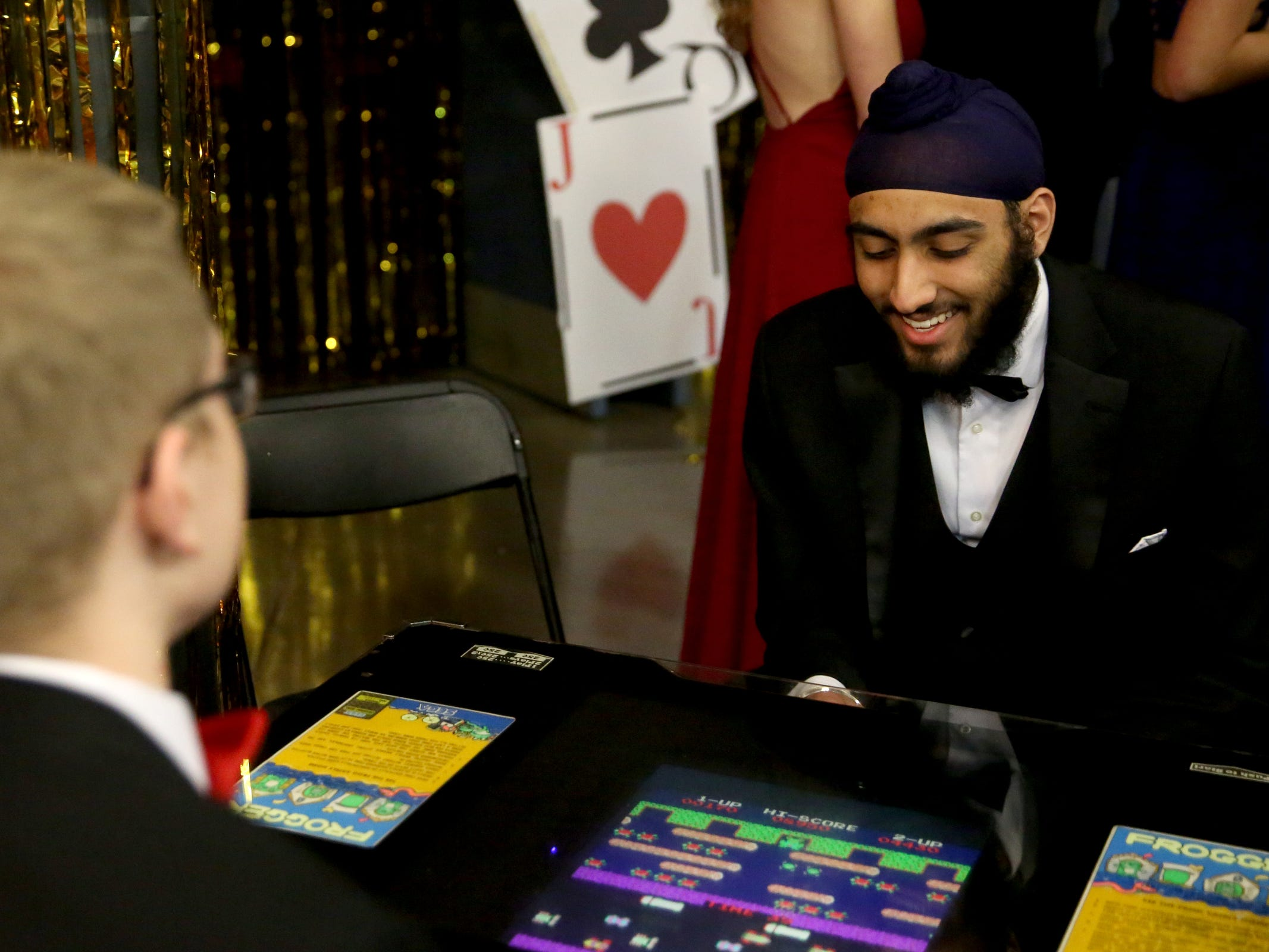 Amrit Singh, facing, and Lane Adams, both seniors, play Frogger during the West Salem High School prom at Salem Armory Auditorium on April 13, 2019.