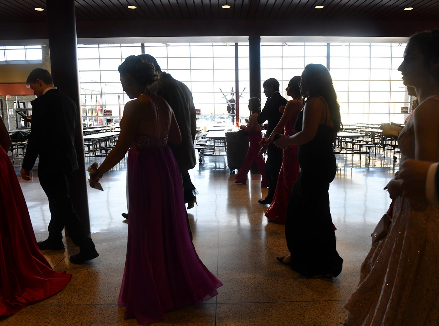 Couples walk to the gymnasium for prom grand march Saturday, April 13, at ROCORI High School in Cold Spring.