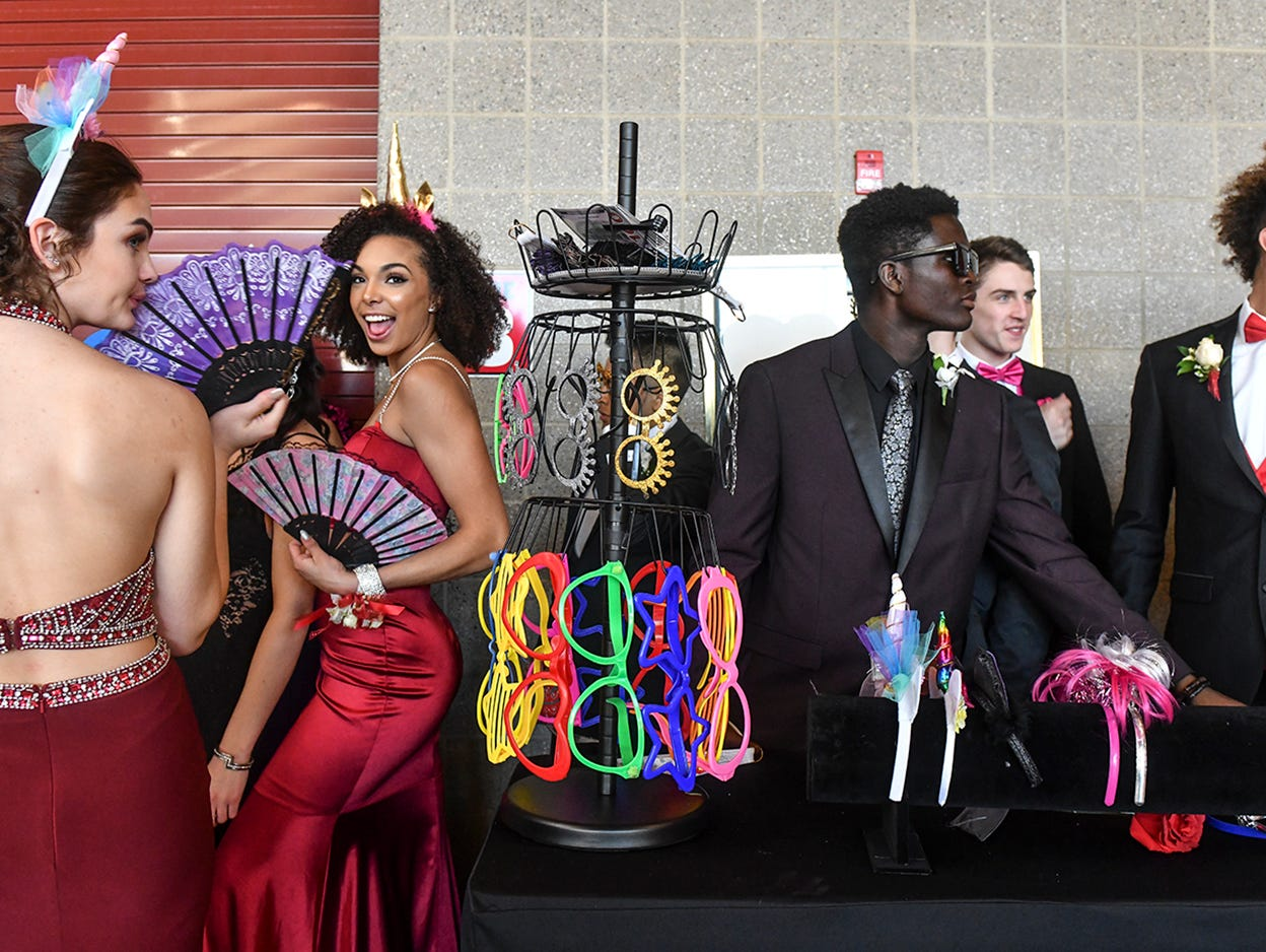 Promgoers try out props for the photo booth during prom grand march Saturday, April 13, at ROCORI High School in Cold Spring.