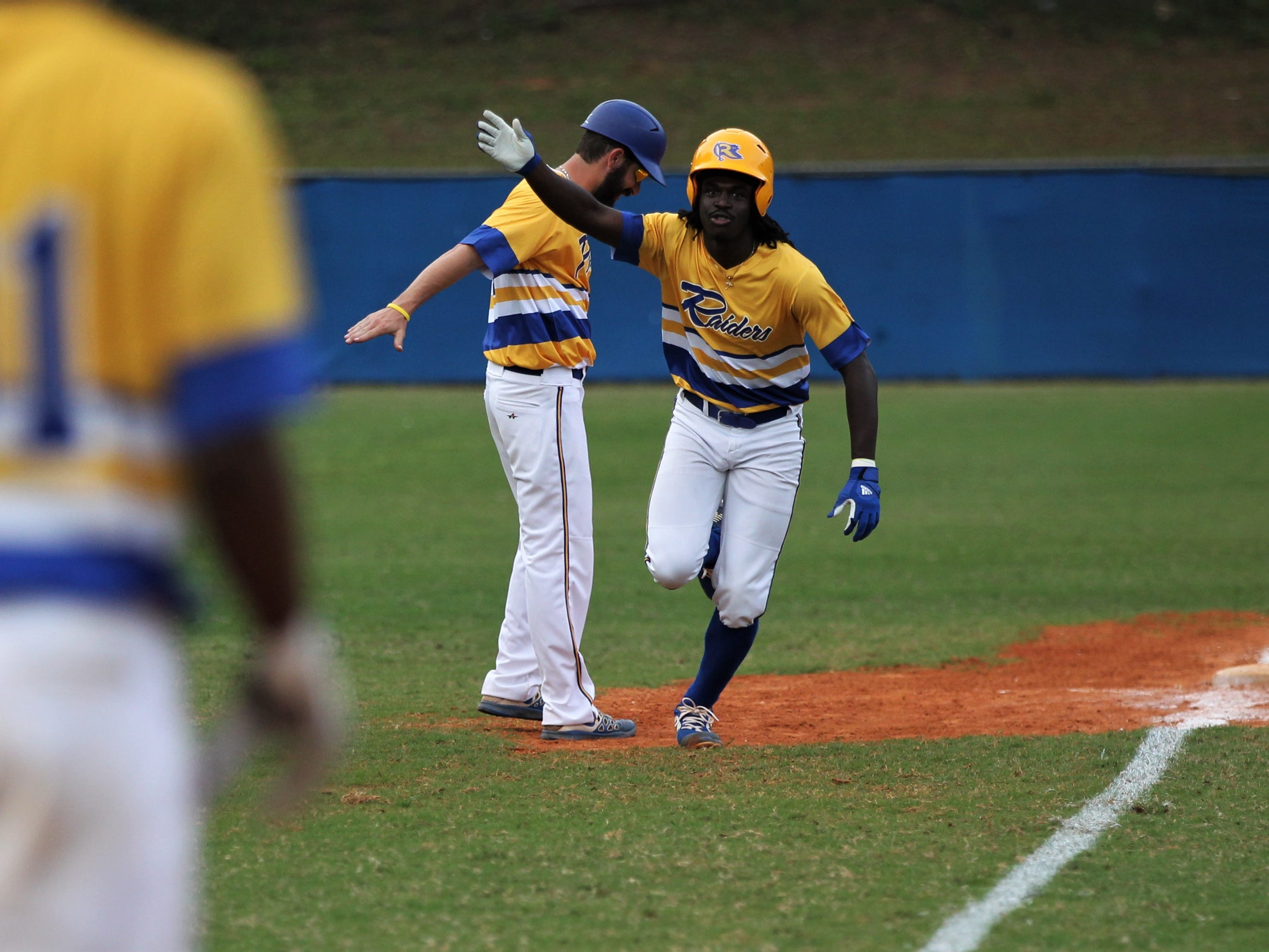 Rickards sophomore Kaleb Henry gets congratulated after a two-run home run as Rickards beat Gadsden County 18-0 in three innings on Friday, April 12, 2019.
