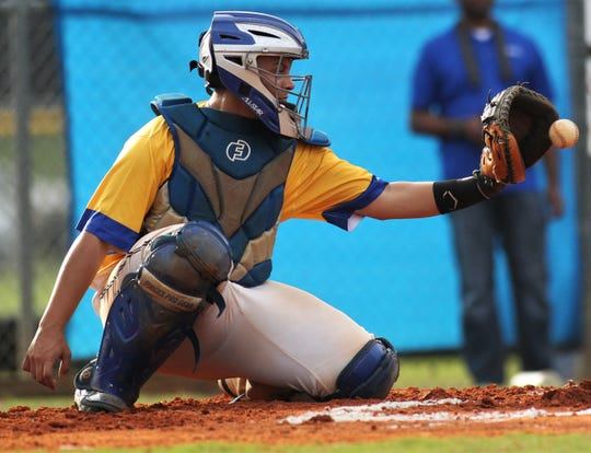 Rickards junior catcher Jayden Figueroa catches a pitch as Rickards beat Gadsden County 18-0 in three innings on Friday, April 12, 2019.