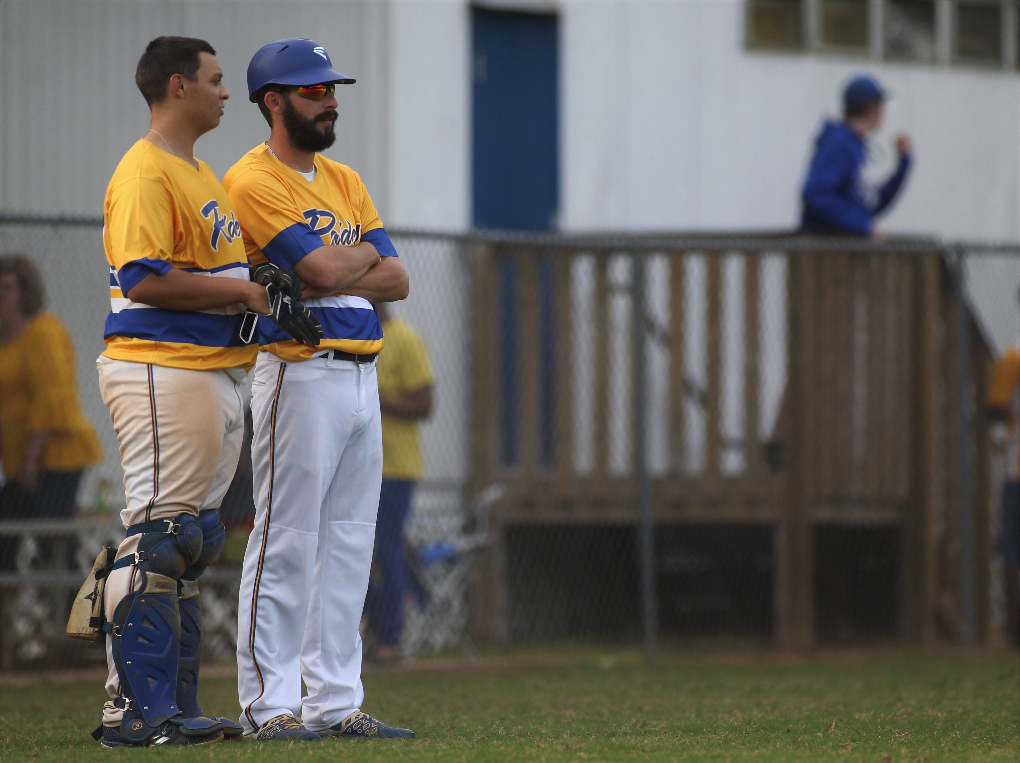 Rickards catcher Jayfen Figueroa talks strategy with his assistant coach as Rickards beat Gadsden County 18-0 in three innings on Friday, April 12, 2019.