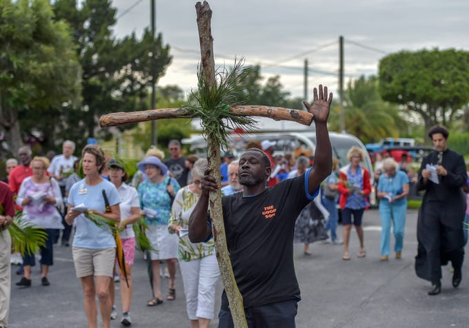 """Dennis Colman (center), of Stuart, carries the cross to the Mount Calvary Baptist Church, the third stop of ten during the Third annual Neighborhood Stations of the Cross prayer walk on Palm Sunday, April 14, 2019, in Stuart. Christians from more than ten area churches walked through streets in Stuart singing and praying, stopping to pray and recite scripture at ten locations, from St. Monica's Episcopal Church in East Stuart to St. Mary's Episcopal Church on Ocean Boulevard. """"We bring together many different churches and we march to pray for peace, and justice, and goodness throughout all our communities,"""" said Father Christian Anderson, of St. Mary's Episcopal Church. """"It's so important because we're building bridges and building more and more community in Stuart,…one whole community together so we can work together for the betterment of Stuart, and not see any divisions, but to see one whole family under God."""""""