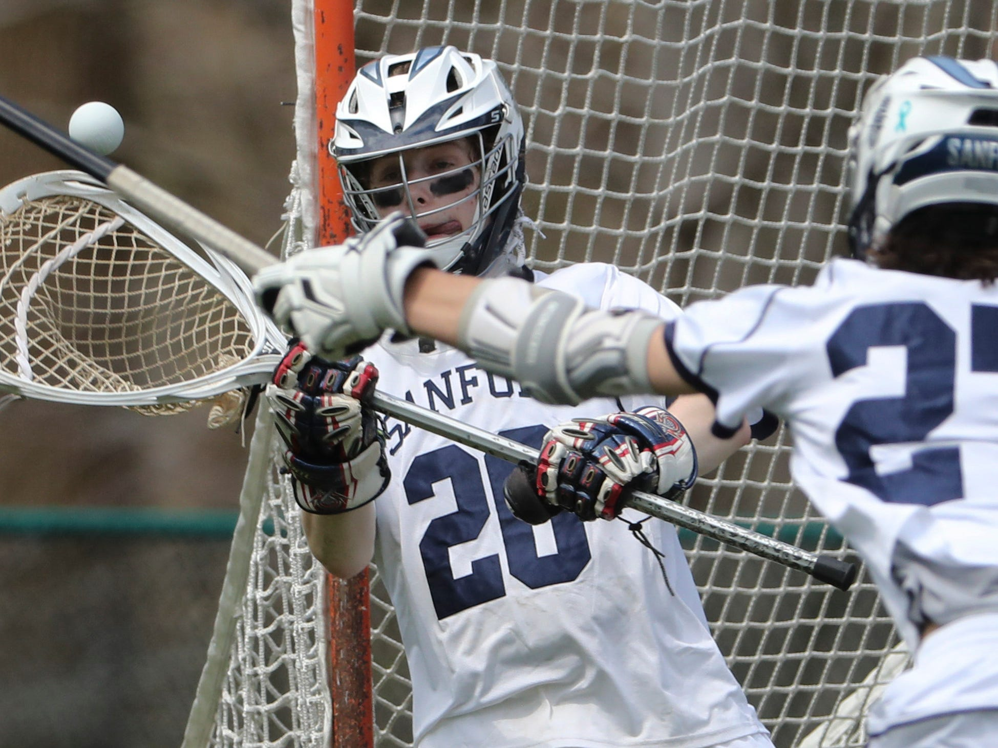 Sanford's Owen Goodier (left) and Nathan LaMonte move to stop a shot in the second half of Sanford's 12-10 win Saturday.
