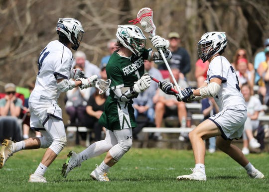 Archmere's Cole Bauer works between Sanford's Jack Leo (left) and Ian Binnersley in the second half of Sanford's 12-10 win Saturday.