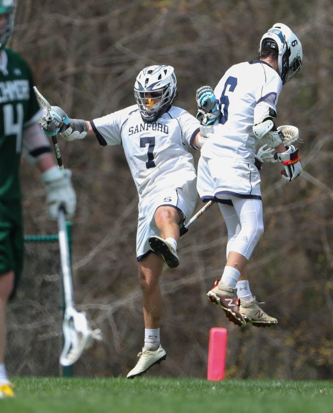 Sanford's Tommy Bloom (left) and Collin Campbell celebrate a goal in the second half of Sanford's 12-10 win Saturday.