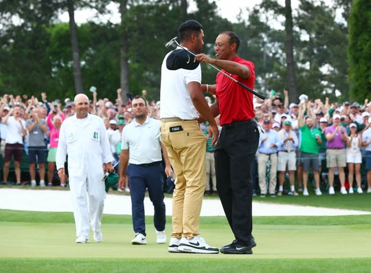 Tiger Woods (right) greets Tony Finau after putting on the 18th green during the final round of The Masters on Sunday.
