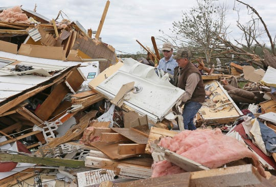 Roman Brown, left and Sam Crawford, right move part of a shower wall out of their way as they help a friend look for medicine in a destroyed home on April 14, 2019 outside of Hamilton, Miss. after an apparent tornado touched down.