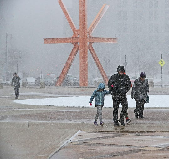 "Gusty winds and wet snow greeted visitors to Milwaukee's lakefront as they walked past the steel sculpture ""The Calling"" by Mark di Suvero located in O'Donnell Park on April 14, 2019. More April snow is forecast in the Midwest this weekend."