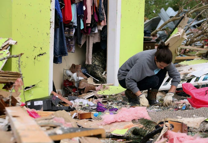 Leslie Harrington kneels down to help a former neighbor and family friend look for jewelry in her destroyed home along Seely Drive outside of Hamilton, Miss., after a deadly storm moved through the area on  April 14, 2019.