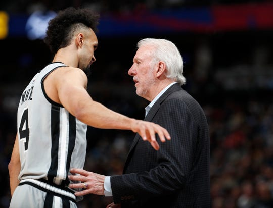 San Antonio Spurs coach Gregg Popovich confers with guard Derrick White during Game 1.