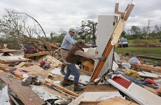 Roman Brown, left, and Sam Crawford, right, move part of a wall out of their way on April 14, 2019, as they help a friend look for medicine in a destroyed home outside of Hamilton, Miss.