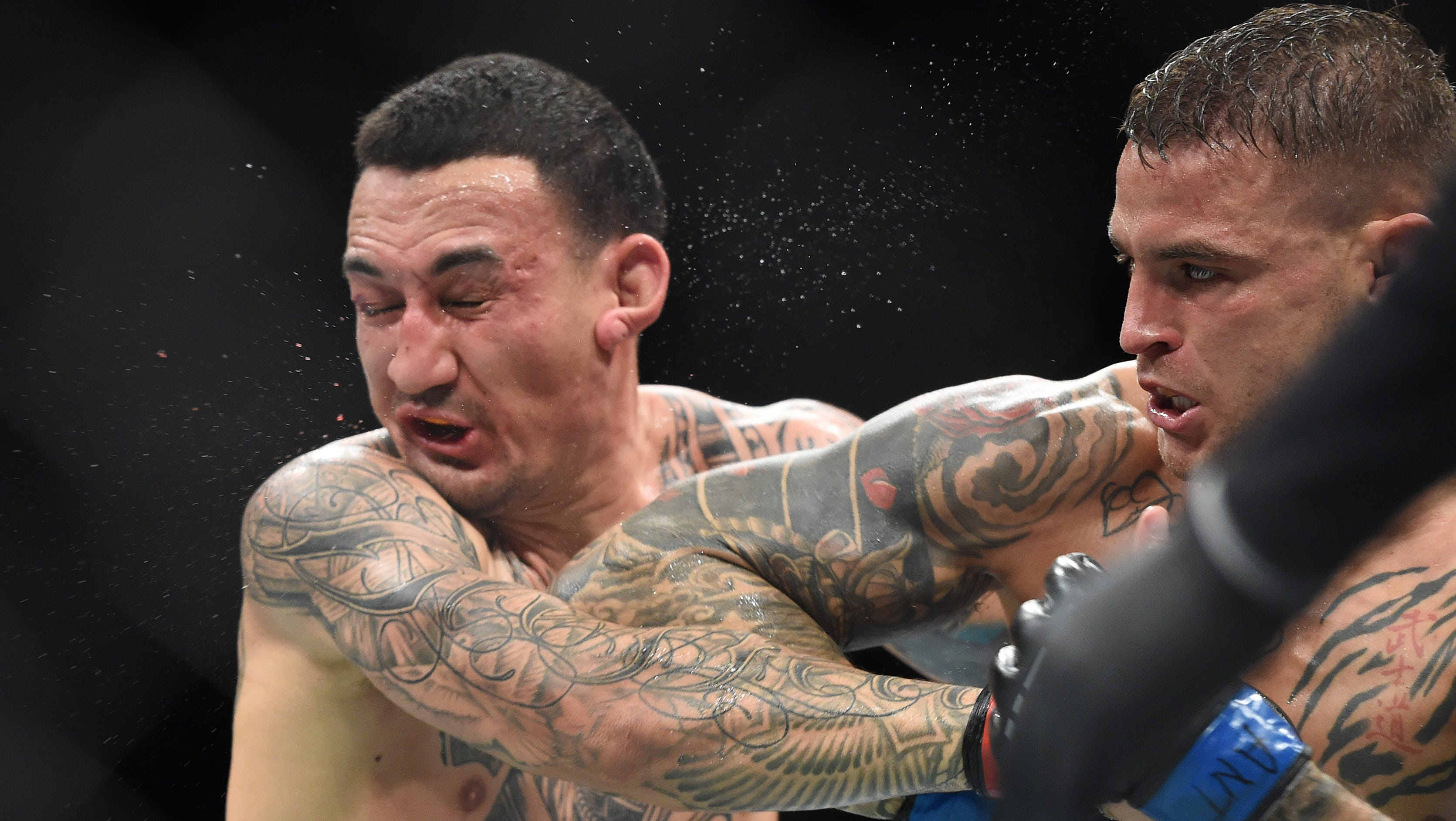 Max Holloway (red gloves) fights Dustin Poirier (blue gloves) during UFC 236.