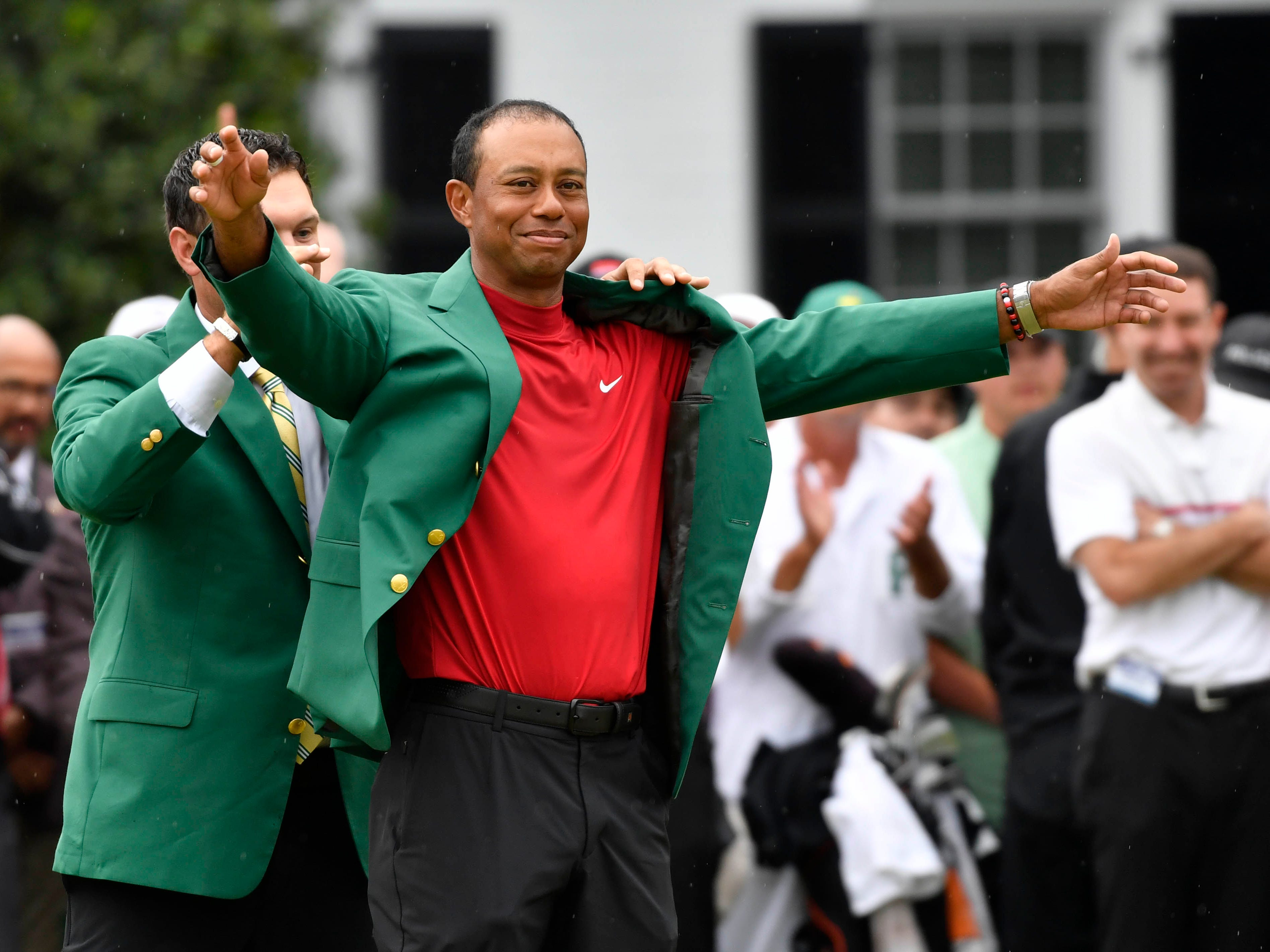 2018 winner Patrick Reed places the green jacket on 2019 winner Tiger Woods, the fifth win at Augusta National in Woods' career.