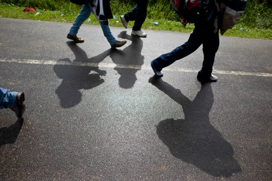 In this file photo, Honduran migrants walk along a road after being deported by bus from Mexico to Corinto, Honduras, near the border with Guatemala. On Sunday, April 14, 2019, Mexican immigration officials said they have sent a group of just over 200 migrants back to Honduras, most of them families traveling with underage children, and that they were flown from the southeastern Mexican state of Veracruz to San Pedro Sula.