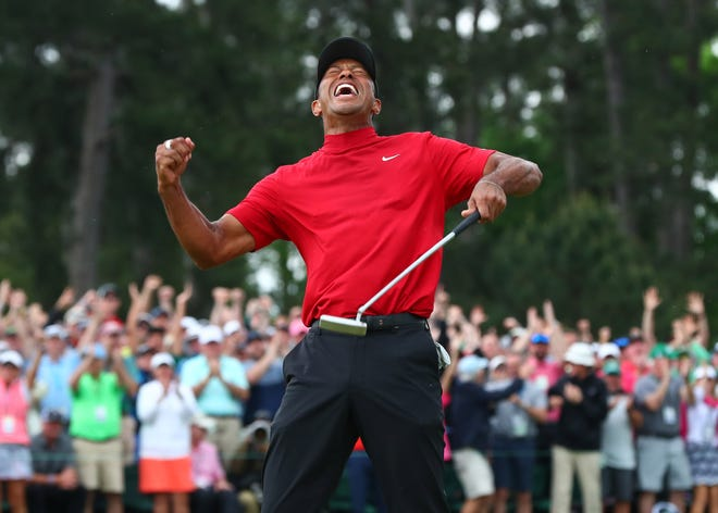 Tiger Woods celebrates after making a putt on the 18th green to win The Masters.