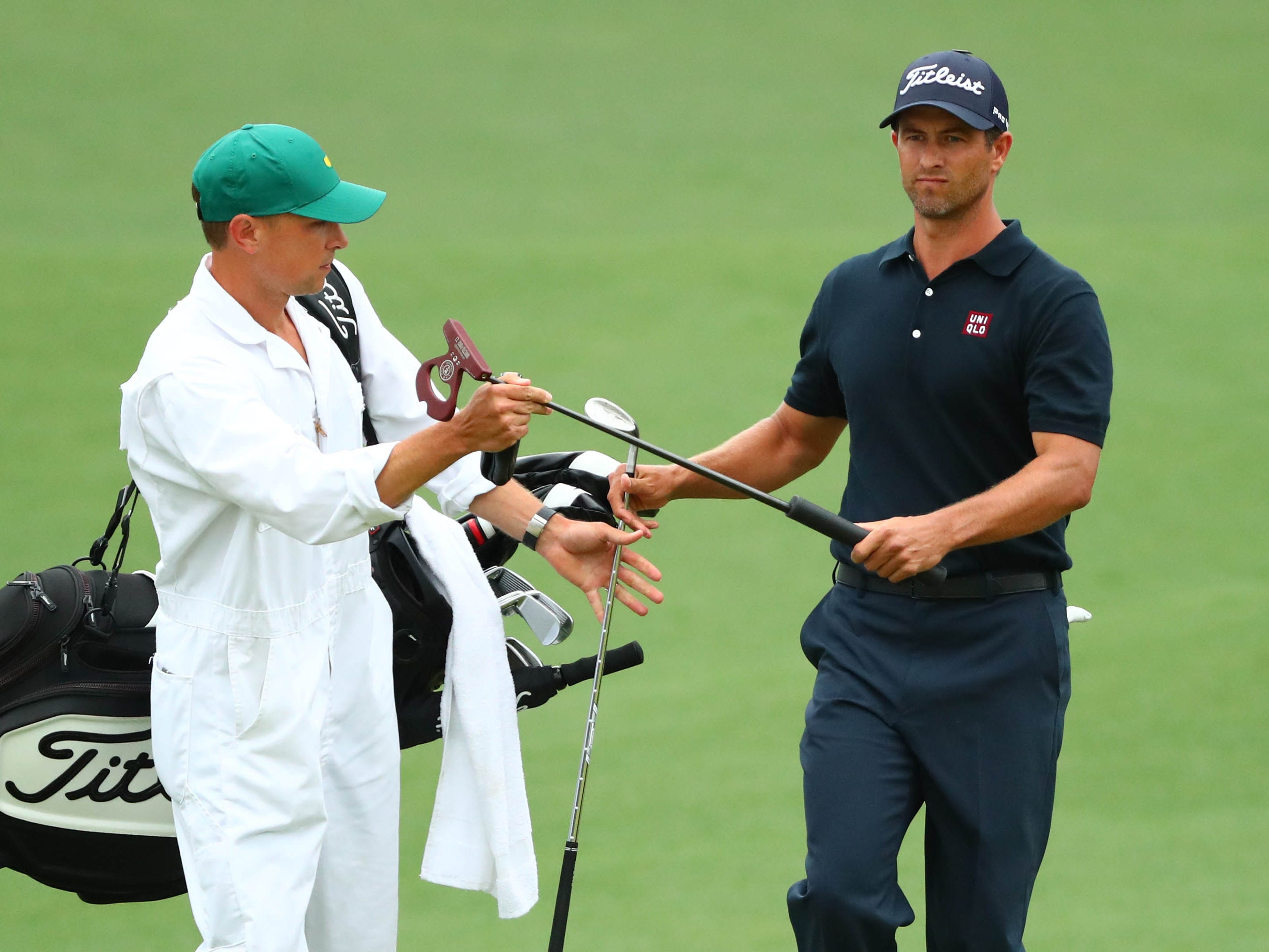 Adam Scott exchanges clubs with caddie John Limanti on the second green during the final round.