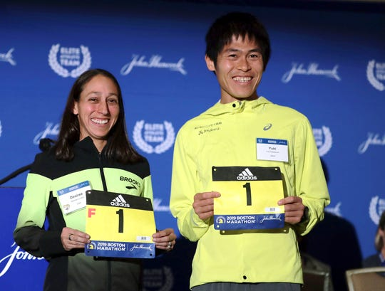 Defending champions Desiree Linden, left, of Washington, Mich., and Yuki Kawauchi, of Japan, display their assigned bib numbers in advance of the 123rd Boston Marathon on Monday.