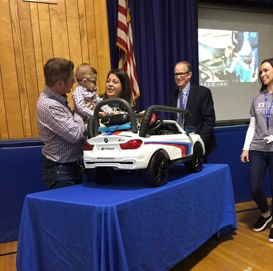 2-year-old Noah Salkowitz and parents Keith and Lisa Salkowitz check out the motorized mini-BMW designed by students at Cove Road School in Hazlet.