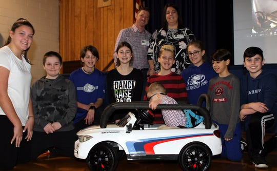 2-year-old Noah Salkowitz settles into a customized mini-BMW designed by students at Cove Road School in Hazlet. Behind him are students on the design team and Noah's parents Keith and Lisa Salkowitz