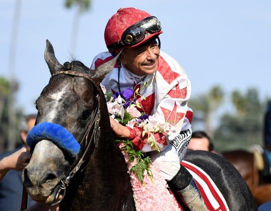 Jockey Mike Smith celebrates after riding Roadster to the win in the Santa Anita Derby horse race at Santa Anita in Arcadia, Calif., Saturday, April 6, 2019.