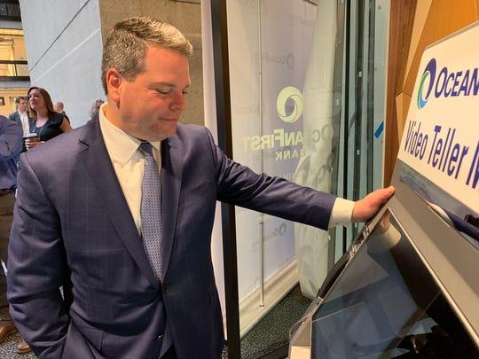 George Destafney, president of OceanFirst Bank's central region, demonstrates a video teller machine.