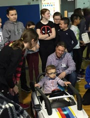 Noah Salkowitz, with dad Keith behind him, settles into the motorized mini-BMW designed by students at Cove Road School in Hazlet.