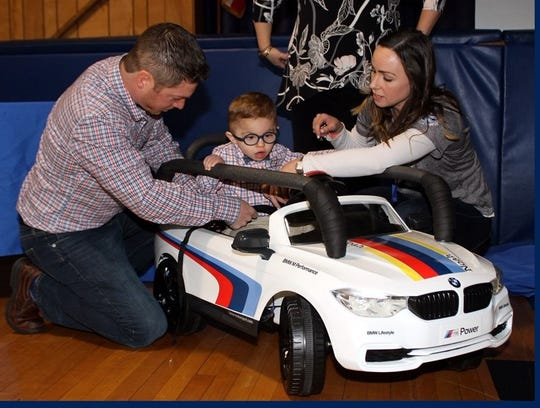 Noah Salkowitz gets into the customized mini-BMW designed by Cove Road School students with help from dad Keith (left) and school LEGO League Club adviser Deahna Grazioli (right)