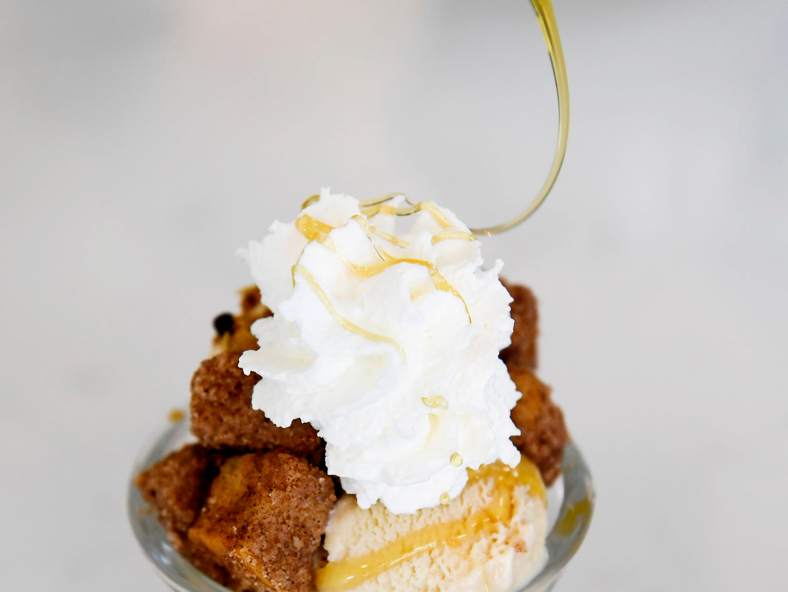 An ice cream sundae is topped with honey at French Broad Chocolates' new Cookies & Creamery on Buxton Avenue April 8, 2019.