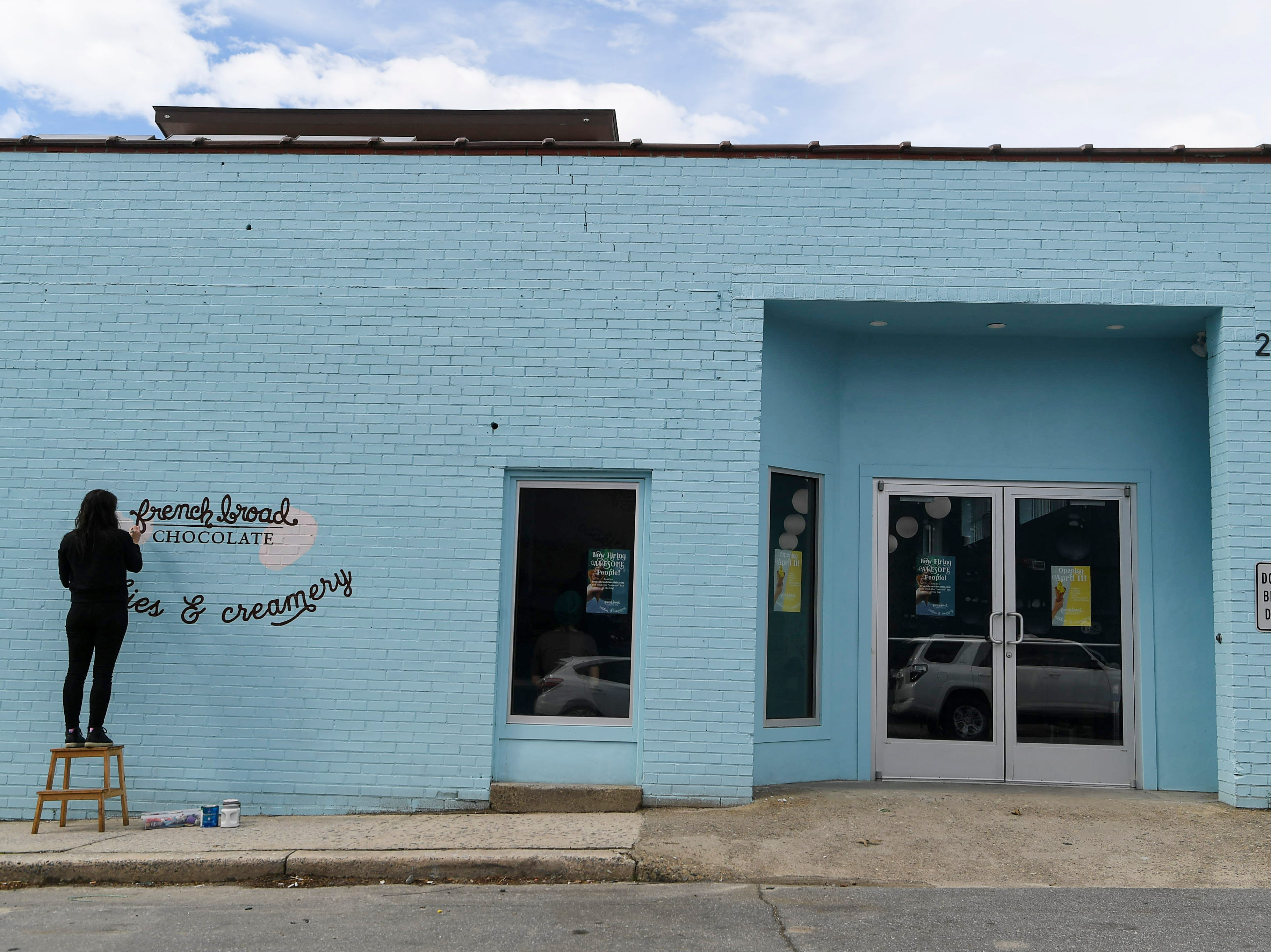 Jael Rattigan, co-founder and CEO, paints a strawberry on the facade of French Broad Chocolates' new Cookies & Creamery on Buxton Avenue April 8, 2019.