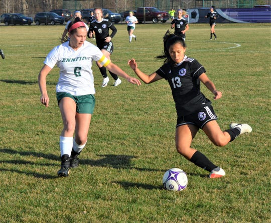 Lakeview's Kirsten Butler brings the ball upfield against Pennfield's Allison Biergeder during this city rivalry contest earlier this season.