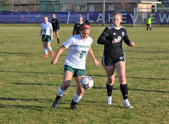 Pennfield's Allison Biergeder controls the ball as she is defended by Lakeview's Kate Hutchins during city rivalry action earlier this season.