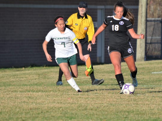Lakeview's Anna Metzger dribbles upfield against Pennfield defender Leah Tharp during city rivalry action earlier this season.