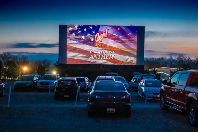 Moviegoers watch the national athem before the start of the featured movie at the Capri Drive-In in Coldwater on Friday, April 5, 2019.