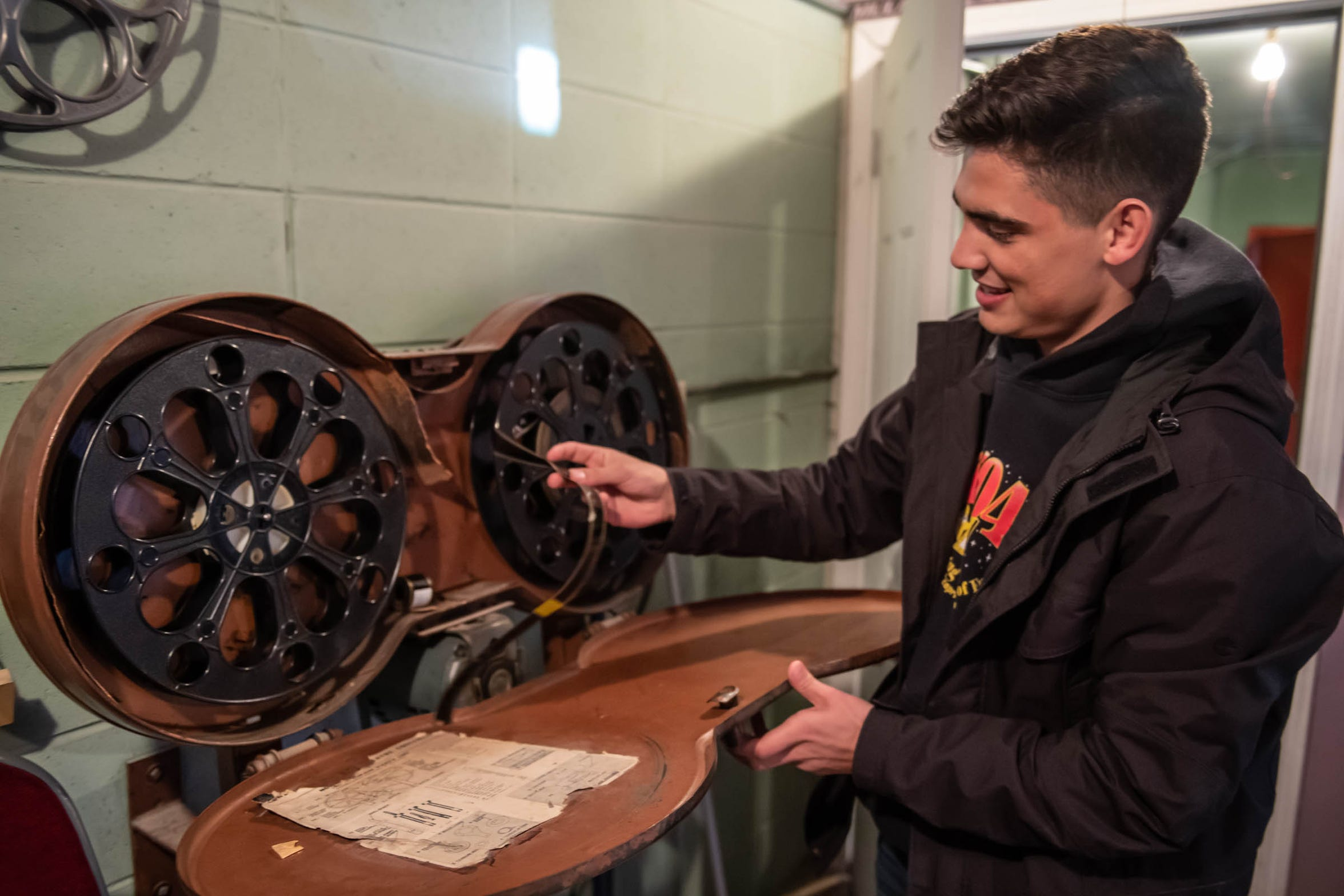Projectionist Michael Magocs shows off film reels that are no longer used at the Capri Drive-In in Coldwater on Friday, April 5, 2019.