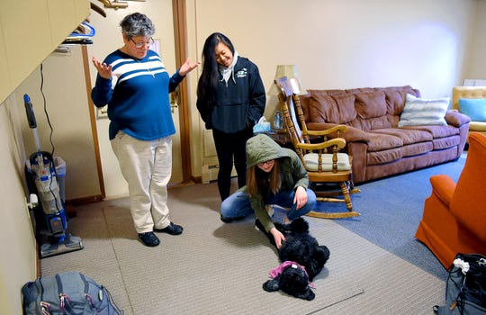 Sister Rose Casaleno, left, and Alyssa Lat, right, watch as Hannah Bronson plays with Tosca, Sister Rose's dog, at the Newman House. Sister Rose serves Director of Campus Ministry at Binghamton University.