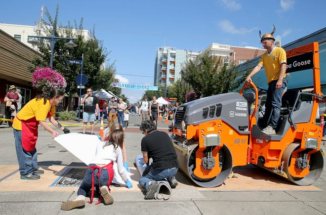 Artist Lana Sheppard , left, gets her ink print ready for printing at the Wayzgoose Arts Festival at Fourth Street and Pacific in downtown Bremerton on Saturday, September 1, 2018. Steamroller driver Reier Reiersgaard .