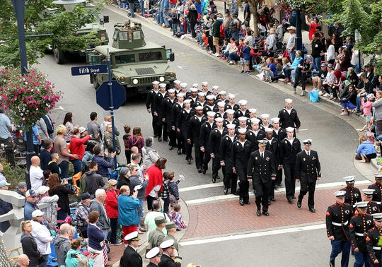 Navy sailors are followed by armored vehicles as they march down Pacific Avenue during the Armed Forces Day Parade in downtown Bremerton, Washington on Saturday, May 19, 2018.