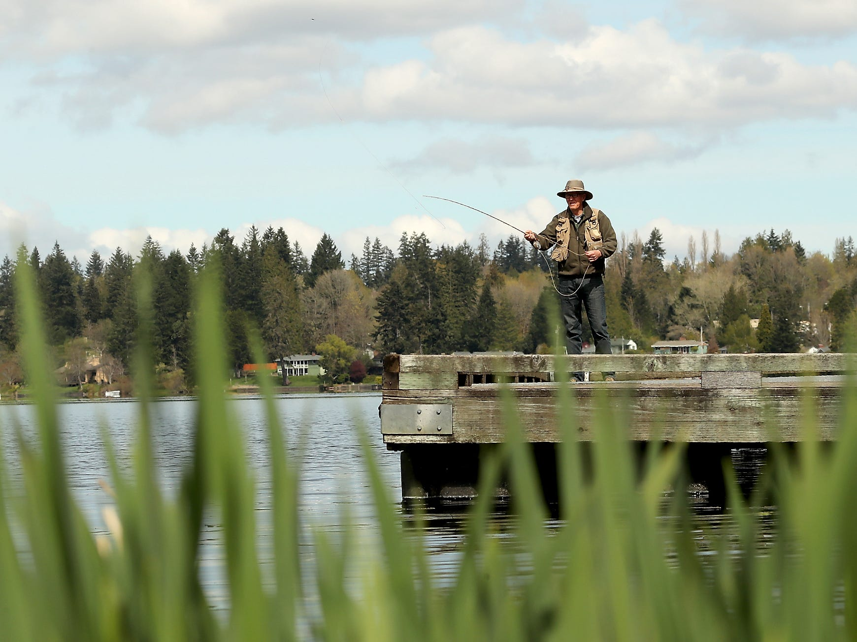 Steve Adamson, of Bremerton, tries out his new fly fishing rod on the dock of Kitsap Lake Park in Bremerton on Monday, April 15, 2019.