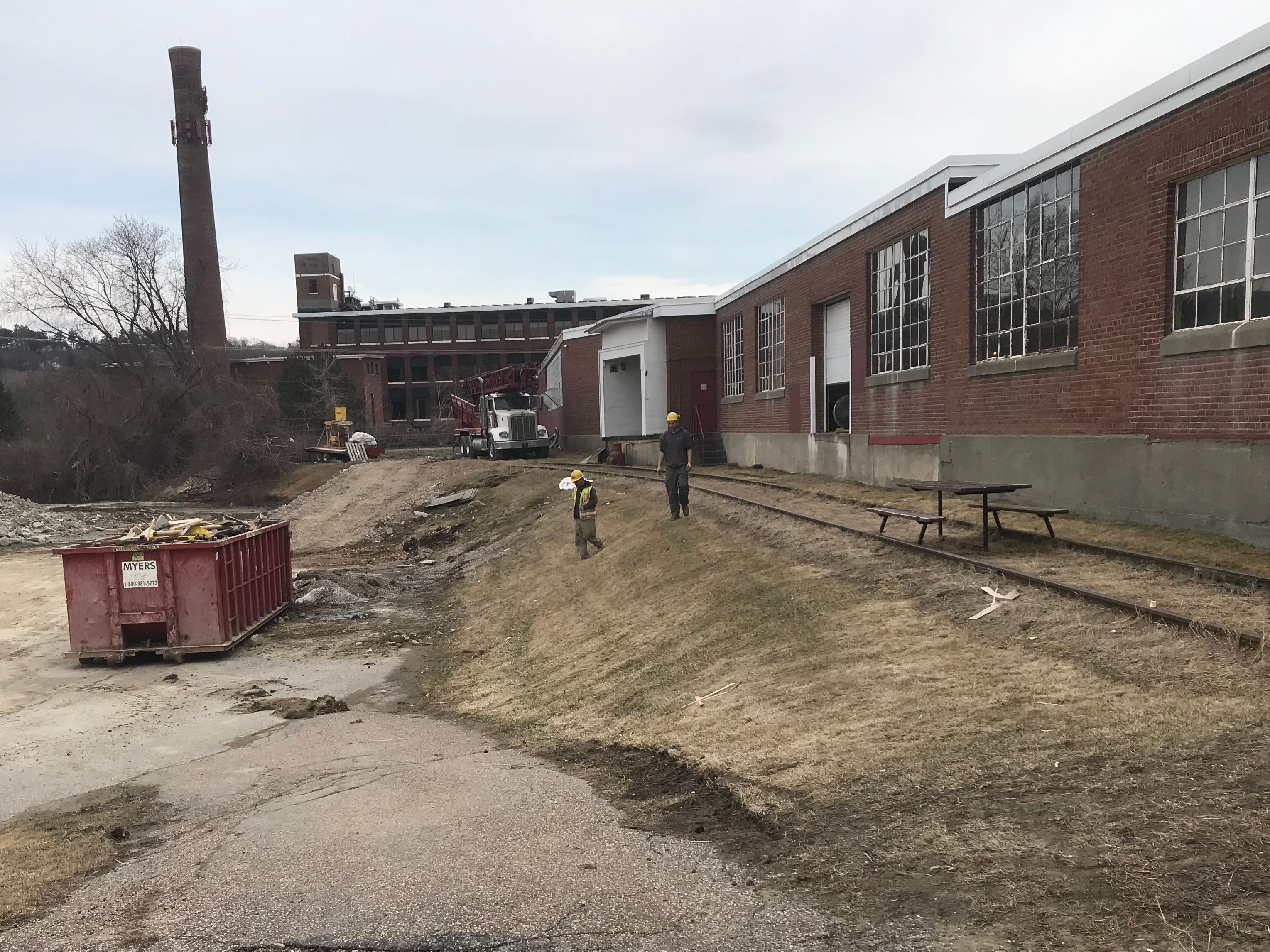 """Work on rehabilitating the former Blodgett Ovens factory in Burlington proceeds on Friday, April 12, 2019. As with the IInnovation Center (rear, marked by a large brick chimney), the new """"Hula Lakeside"""" development will tap into groundwater for cooling and heating systems."""