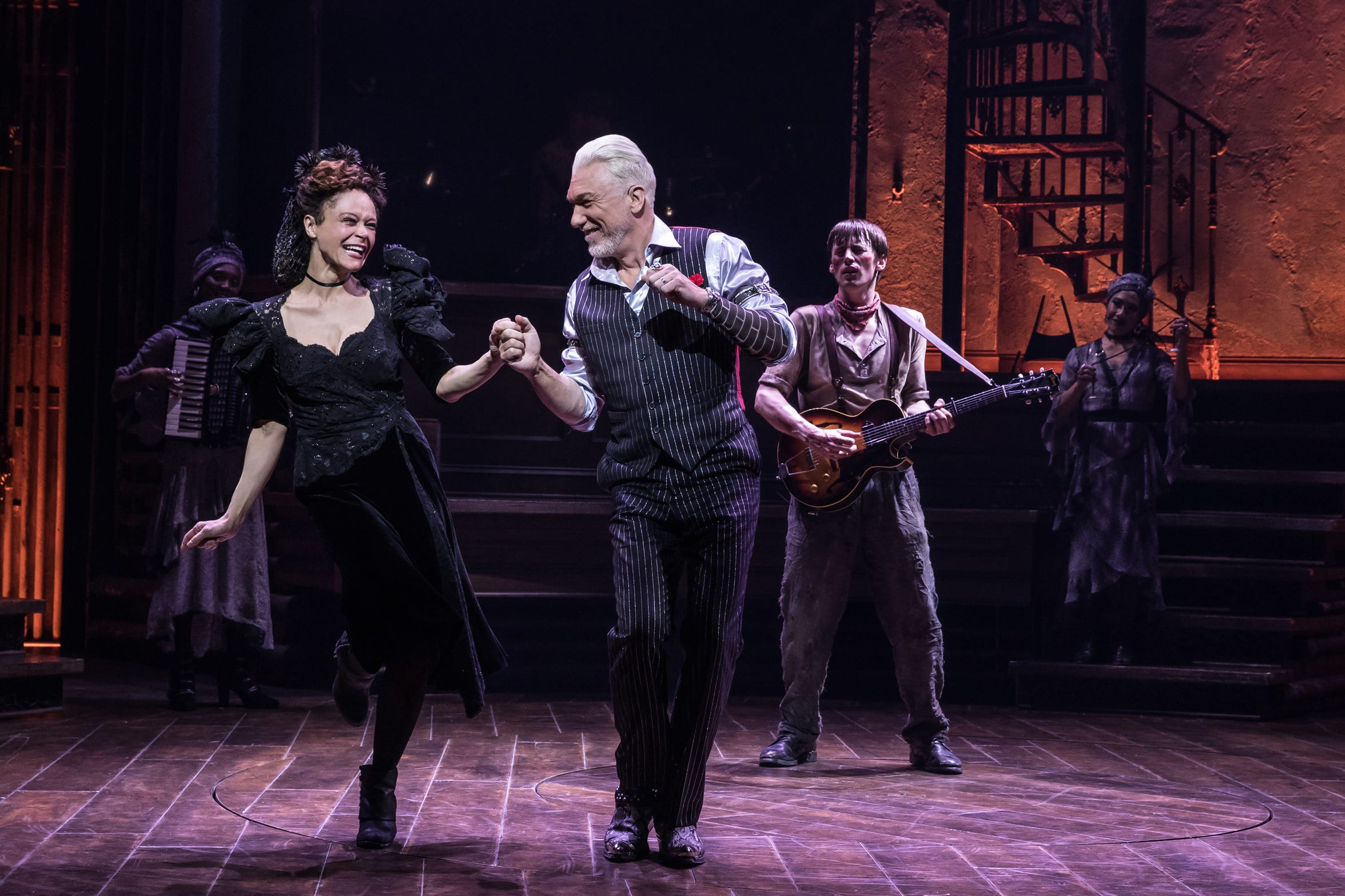 "Amber Gray as Persephone and Patrick Page as Hades dance while Reeve Carney as Orpheus plays guitar in the Broadway production of Anais Mitchell's ""Hadestown."""