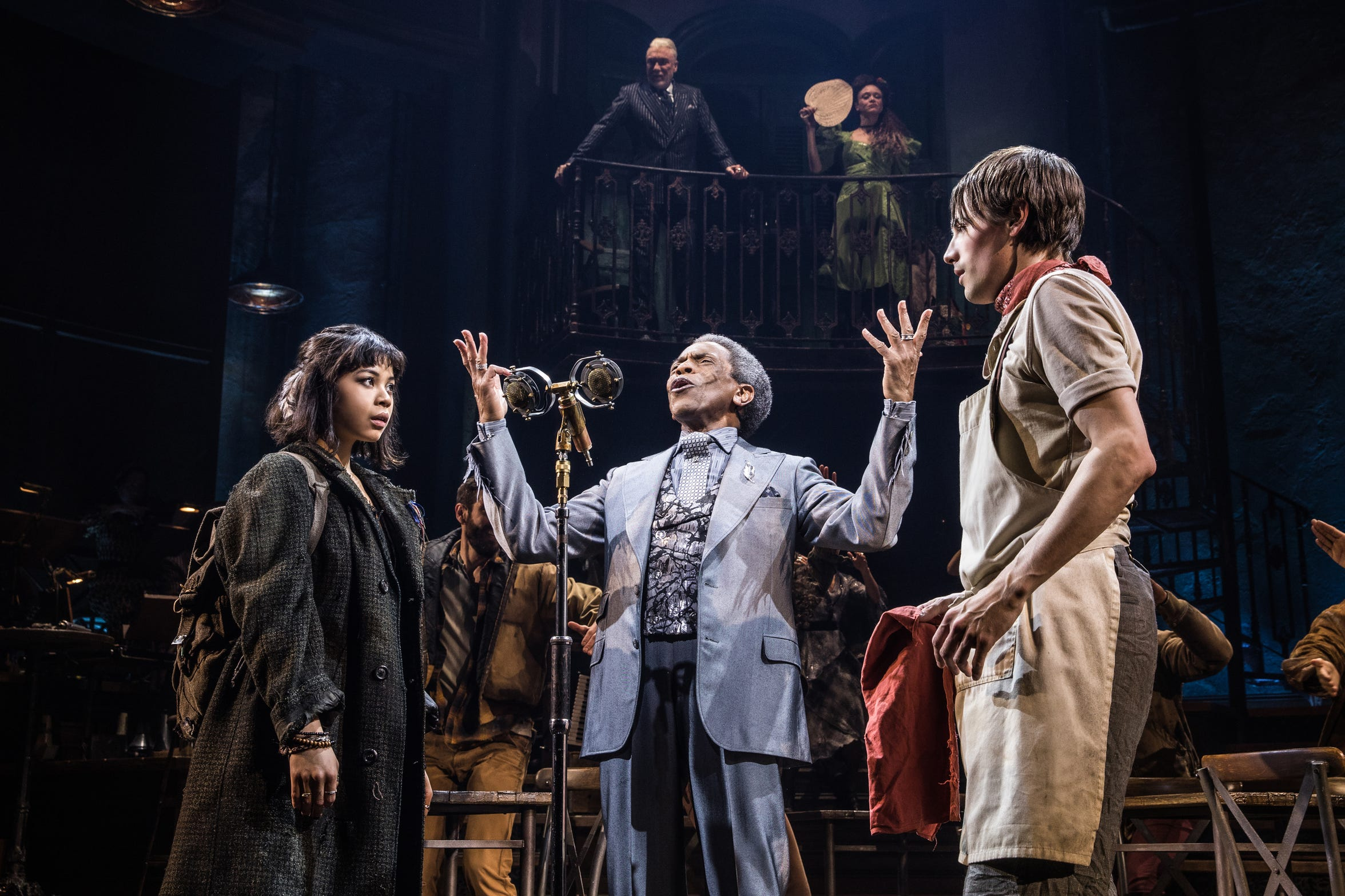 "From left to right, Eva Noblezada as Eurydice, Andre De Shields as Hermes and Reeve Carney as Orpheus perform while Patrick Page as Hades and Amber Gray as Persephone look on from the balcony in the Broadway production of Anais Mitchell's ""Hadestown."""