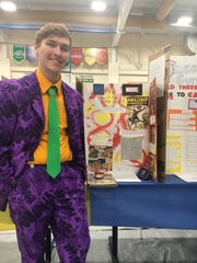 Clermont Northeastern High School junior Noah Witt stands in front of his display on the rivalry between DC Comics and Marvel Comics.