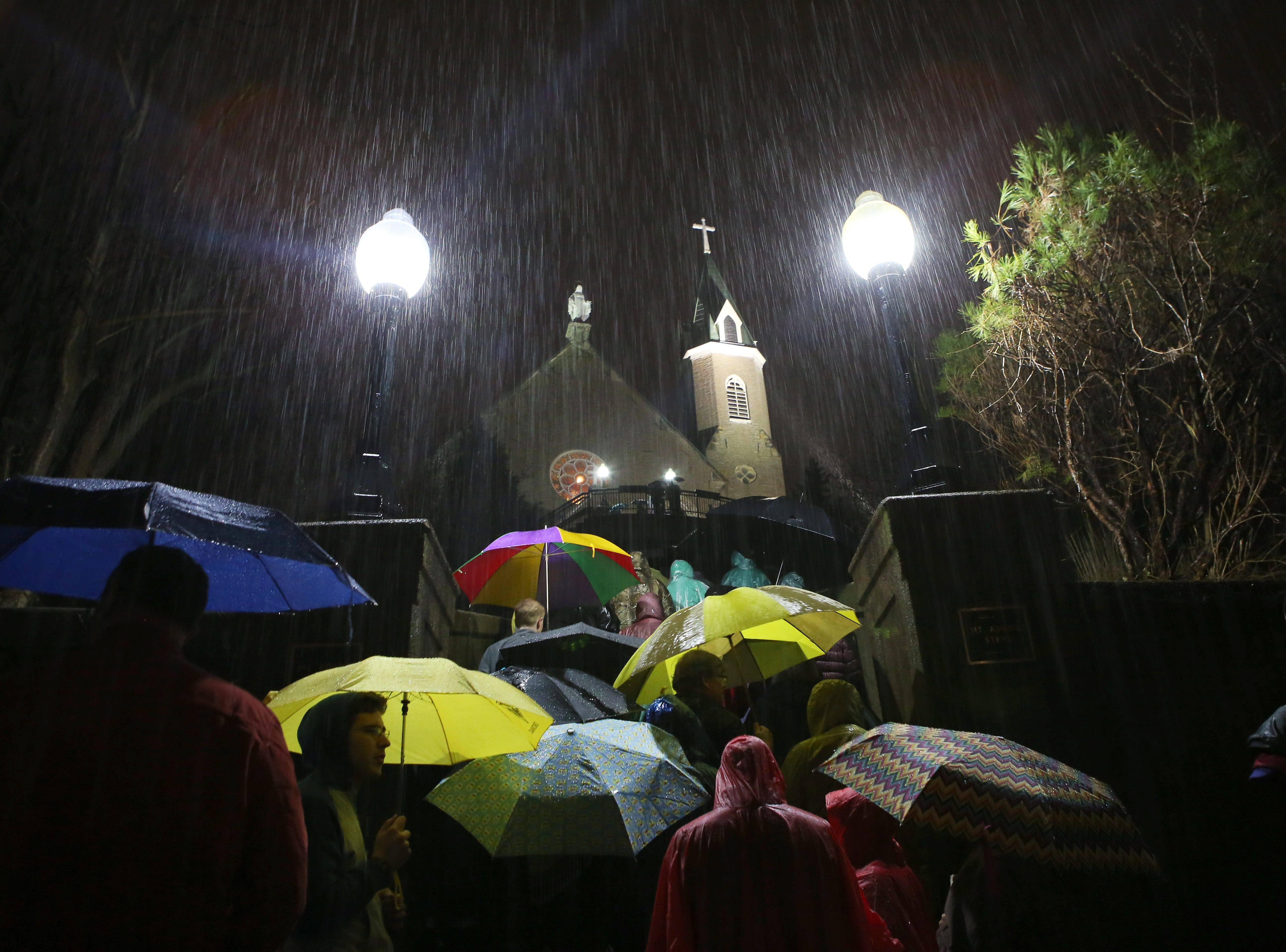 Despite the rain, people gather at midnight to pray the steps of Holy Cross-Immaculata Church in Mt. Adams Friday, April 3, 2015. This Good Friday pilgrimage was started approximately 150 years ago and draws thousands to pray the steps all day.