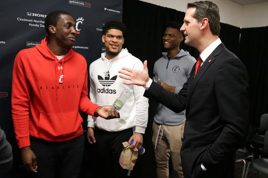 John Brannen talks with Cincinnati Bearcats players Keith Williams, Jarron Cumberland and LaQuill Hardnett after he is introduced as men's basketball head coach at the University of Cincinnati, Monday, April 15, 2019, at Fifth Third Arena in Cincinnati. Brannen formerly coached at Northern Kentucky University.