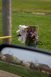 """Michael Strouse's neighborhood on Bluffs Drive is reflected in a vehicle mirror. Ellen """"Ellie"""" Weik's remains were discovered across the street near Millikin Road. Loved ones placed flowers and stuffed animals nearby."""