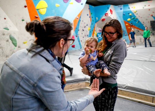 Jenni Montague, left, plays with the toes of her daughter Hero Montague while Jamie Watson, an employee, holds up Hero at Clarksville Climbing on Monday, April 1, 2019.